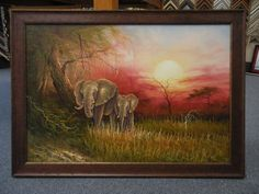 A beautiful painting of elephants accented by a distressed wood frame