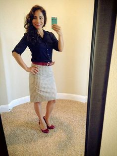 Printed cream skirt, navy top, red belt, red shoes.