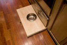 Detail shot showing pull-out dog dish from base cabinet toe kick.
