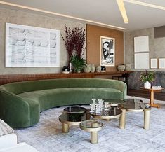 Olive green curved couch and five circular coffee tables matched in different sizes