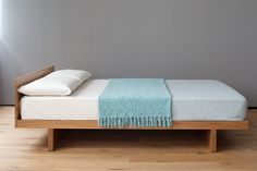 The Kyoto is a Japanese Bed with headboard - a low, modern platform bed in solid wood with a generous headboard panel. Made in the UK. Buy online.