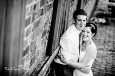 Summer wedding, smiling bride and groom outside the Chainshop at Avoncroft Museum of Historic Buildings (avoncroft.org.uk). Black and white photograph. Rob & Sarah Gillespie Photographers.