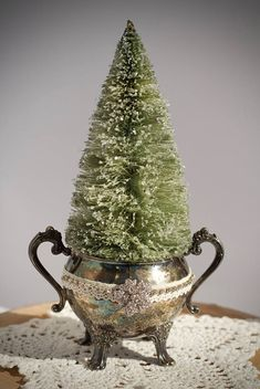 A vintage tarnished silver sugar bowl is embellished with lace ribbon, a stand of rhinestones and a rhinestone button. The bottle brush tree is a silvery green that sparkles with a dusting of glitter.