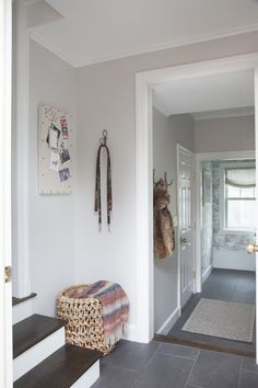 Beautiful foyer features walls painted light gray, Benjamin Moore Balboa Mist, lined with Anthropologie Equestrian Hook over Basaltina Porcelain Tiled floor.