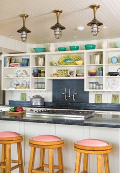 Open kitchen shelves offer both functional storage and a place to display vibrant turquoise and yellow tableware in this coastal cottage kitchen.