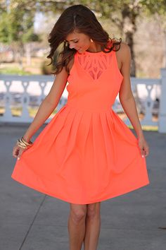 bright coral dress with sheer neckline detail.