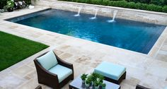 Photo slideshow of Artistic Gardens' design projects: seating area on flagstone terrace surrounding swimming pool with fountain spouts