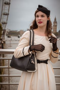Vintage blogger RetroCat with a nude coloured retro dress, nylon gloves, and a vintage hat in London / UK