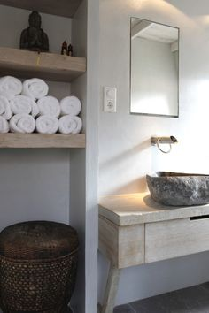 Zen bathroom features rectangular mirror over washstand with gray stone vessel sink paired with wall-mounted faucet next to alcove filled with rustic floating shelves filled with towels, Buddha and woven hamper. Asian Bathroom, Zen Bathroom, Bathroom Toilets, Bathroom Shelves, Earthy Bathroom, Concrete Bathroom, Natural Bathroom, Minimal Bathroom, Stone Bathroom