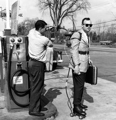 A salesman has his motorized roller skates refueled at a gas station (1961)