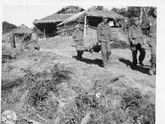 WWII soldiers carry a litter patient through  Burmese village on the way to the L-5 strip for evacuation from Namhkam. Photographer Unknown