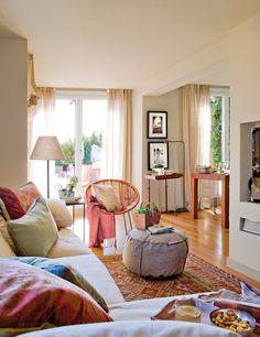 Salón con sillón en L y sillón de bambú. Salón pequeño con alfombra étnica, puf de tela y vistas a la terraza