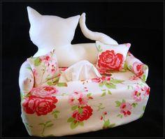 Ein Sofa mit einer weißen Katze als Rückenlehne und 2 losen Kissen auf Rosen gebettet.    Der Bezug wird einfach über die Box gestülpt und ist passend