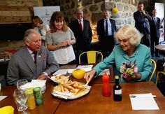 Camilla Parker Bowles Photos - Prince Charles, Prince of Wales and Camilla, Duchess of Cornwall are served fish and chips in Aberdaron during a visit to the Welsh Village on July 5, 2016 in Aberdaron, England. The Prince Charles, Prince of Wales and Camilla, Duchess of Cornwall are on the second day of their annual visit to Wales. - Prince Of Wales & Duchess Of Cornwall's Annual Summer Visit To Wales
