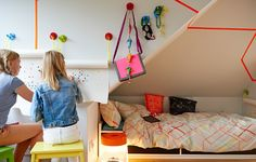 View of colorful bedroom with kids' drawing with felt-tip pens on to MALA drawing paper roll on wall. BEKVAM step stools.
