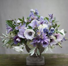 Ariella Chezar, flower arrangement in a compote vase with lavender and white anemones, clematis, delphinium and silver foliage