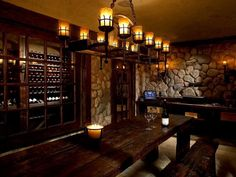 Large wine tasting room design in stone and wood with one wall lined with custom wine storing cabinets.