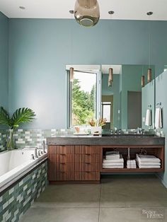 The off-center look of an asymmetrical vanity adds a lyrical quality to this nature-inspired bathroom. Drawers outfitted with storage containers hold bathroom essentials while fluffy white towels find a home on the shelf below the sink.