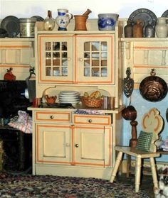 """WOODEN KITCHEN <=> CLOSE-UP Kitchen in the original paint scheme of yellow and sponged-on blue with orange details, printed paper """"tile"""" floor, 31½ inches across the front base; side walls angle towards the back wall; original furnishings consist of 4 hanging shelves, cupboard with glass upper doors, bench, work table with shelf, 2 side chairs; German, maker not identified, late 19th century; the tin stove and sink have been added to the kitchen furnishings"""