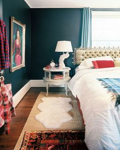 Love the mix here...and easily achieved with flea market finds: headboard, rugs, funky painted vintage lamp, plaid blanket. Not to mention...that deep wall color is off the hook! House of Turquoise