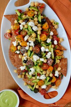 Add a fresh twist to a comfort food favorite with a recipe for Greek nachos topped with an herbed tahini sauce and veggies.