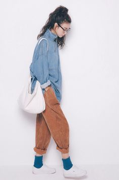 This model is wearing corduroy pants with a denim jacket. These are both moderately crisp fabrics, as they stand just enough away from the body to conceal body shape. The pants add size to her legs, making them appear larger. The fabric seems thick and firm.