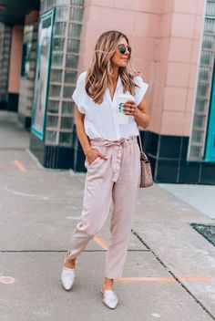 A Month's Worth Of Chic Spring Outfits: Fashion blogger 'Cella Jane' wearing a white short sleeve blouse, blush belted ankle pants, metallic mules, round aviator sunglasses and a blush studded bag. Spring outfits, casual outfits, fashion trends 2018, casual outfits, simple outfits, comfy outfits, vacation outfits, summer outfits, #fashion2018 #casualstyle #springstyle #streetstyle #ootd #fashionblogger #blush
