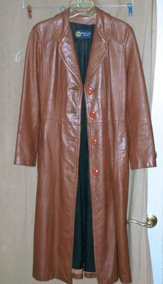 """Vintage Long Leather coat by Winners Circle Fashion  outstanding Long leather coat calf length for most duster style  looks great with boots esp 45"""" long 16"""" cross shoulders 23"""" sleeve length id say for SMALL lady  Beautiful long leather coat. shows slight wear and been stored, still great condition fully lined and one beautiful coat as i recall it has a tie belt same color n material  questions ask... will post more pics n bac…"""
