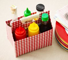Double-smart: Reusing a six-pack container as a condiment caddy, but covering it with oil-cloth instead of paper so it's wipe-clean. Even sturdier with a rope-wrapped handle!