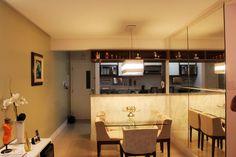 O balcão tem tampo de granito e base revestida de papel de parede e, na face virada para a cozinha, tem armário com gavetas. O nicho acima da bancada é uma parte de um armário que foi fixado na viga de concreto. A mesa de vidro quase desaparece e não pesa no ambiente.