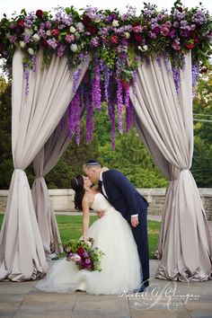 Beautiful canopy chuppah at Casa Loma loaded with hanging purple wisteria, garden roses and foliage.