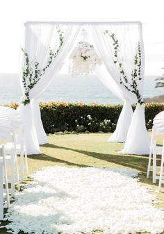 Wedding arch, wedding chuppah with flower chandelier. White modern wedding with full aisle petals. Vines on arch with draping fabric and chandelier  -Florals by Jenny -Mink Photography -Montage Laguna Beach
