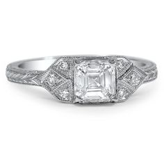 The crisp lines of the 1920′s Wen Ring provide the perfect display for a sparkling asscher cut diamond. Eight round brilliant diamond accents adorn the shoulders and gallery, while milgrain detailing and vine engravings give the design extra vintage allure.