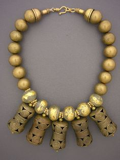 Five hollow cylindrical brass pendants from the Baule tribe of the Cote d'Ivoire (Ivory Coast) hang from some old and unusual recycled bottle glass beads with strong remnants of gold foil. g6010.jpg (525×700)