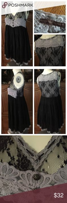 """Anthropologie HAZEL Black Ribbons and Lace Dress Anthropologie HAZEL fully-lined v-neck empire waist Black Lace dress w/lace panels across chest/back & trimmed in a gray lace appliqué band under the bust/top of back. Black satin ribbon weaved along neckline. 3 buttons in the front. Tiered black lace skirt portion w/a bottom gray lace trim. 85% Cotton; 15% stretch Polyester. Flat: 16-1/2"""" under arms across bust; 21-1/2"""" across waist; 32-1/2"""" shoulder to bottom hem. In excellent preowned…"""