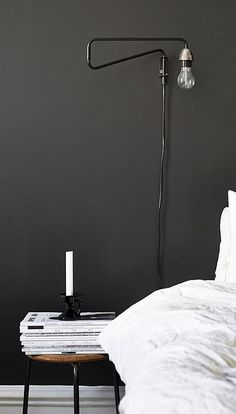 = black wall, mounted bedside lamp and white linen