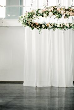 Indoor ceremony backdrop with simple white fabric and a hanging floral ring chandelier