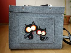 A briefcase, gray and black, with two cats on it, made almost entirely with felt.