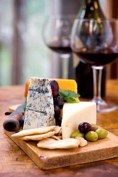 Cheese and Wine! A cheese plate of Bleu, Swiss and Cheddar cheeses served with crackers, macrona almonds and fruit.