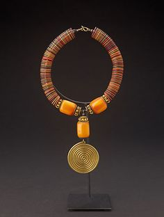 www.africaandbeyond.com. Amber Necklace. Hand made in the Turkana style of northern Kenya featuring faux amber and a magnificent brass swirl design to anchor the piece.
