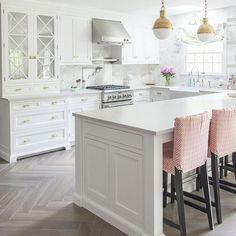 White kitchen with bleached hardwood flooring in herringbone pattern.