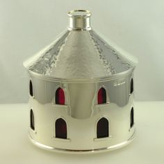 Silver condiment in form of stylised house with claret coloured glass liner