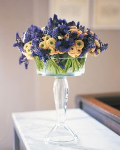 Flowers in a Glass Compote Here, brilliant violet Muscari latifolium and tight blooms of Ranunculus get a boost in a lush, dense display.  floral arrangement