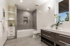 Contemporary Full Bathroom with Double sink, Limestone counters, Wall sconce, tiled wall showerbath, Built-in bookshelf