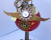 Flight 15: Silver finished composite bird mounted on #15 red and white billiard ball mounted on an old oil can. Oil can base has bow and arrow, with a vintage button - bulls eye pattern, and has a metal arrow pointer with bicycle and watch gear charms at back. More description and pricing on #ETSY