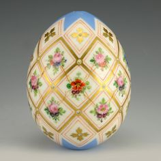 A Russian porcelain Easter egg, circa 1900. The pale blue ground egg decorated with vibrant floral sprays against a white ground within gilded diamond shaped borders.