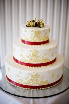 Classic and elegant Indian inspired red and gold wedding cake with a mehndi paisley design