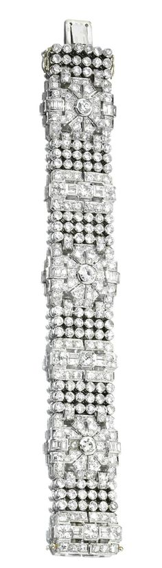 DIAMOND BRACELET,  CIRCA 1930.  The articulated band composed of six open work geometric links set with baguette, circular-, brilliant, and single-cut diamonds, spaced by a stylised mesh of collet-set similar stones, mounted in platinum, length approximately 180mm, French assay and indistinct maker's marks.