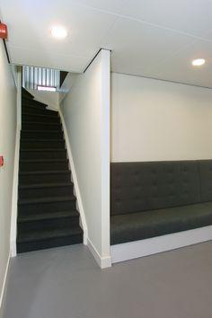 Houten trap, bekleed met zwarte vloerbedekking grafisch ingedekt door gestuckte wanden. SLB diensten, Amsterdam.
