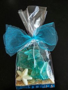 SEA GLASS CANDY, WHITE CHOCOLATE STAR RISH CANDY AND BROWN SUGAR SAND, i WOULD TIE WITH JUTE WITH LITTLE REAL SHELLS TIED ON THE ENDS RATHER THAN THE BLUE NETTING.
